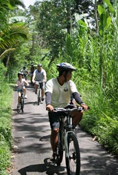 Cycling through green countryside village with little children